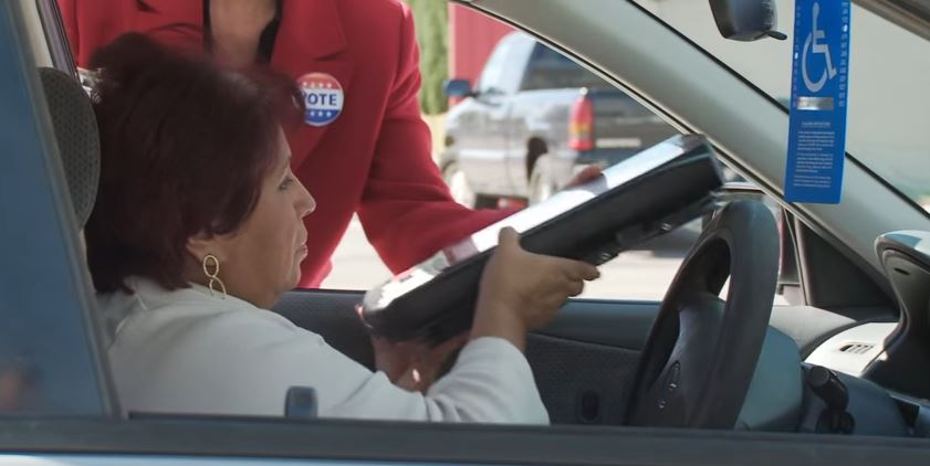 woman in car curbside voting