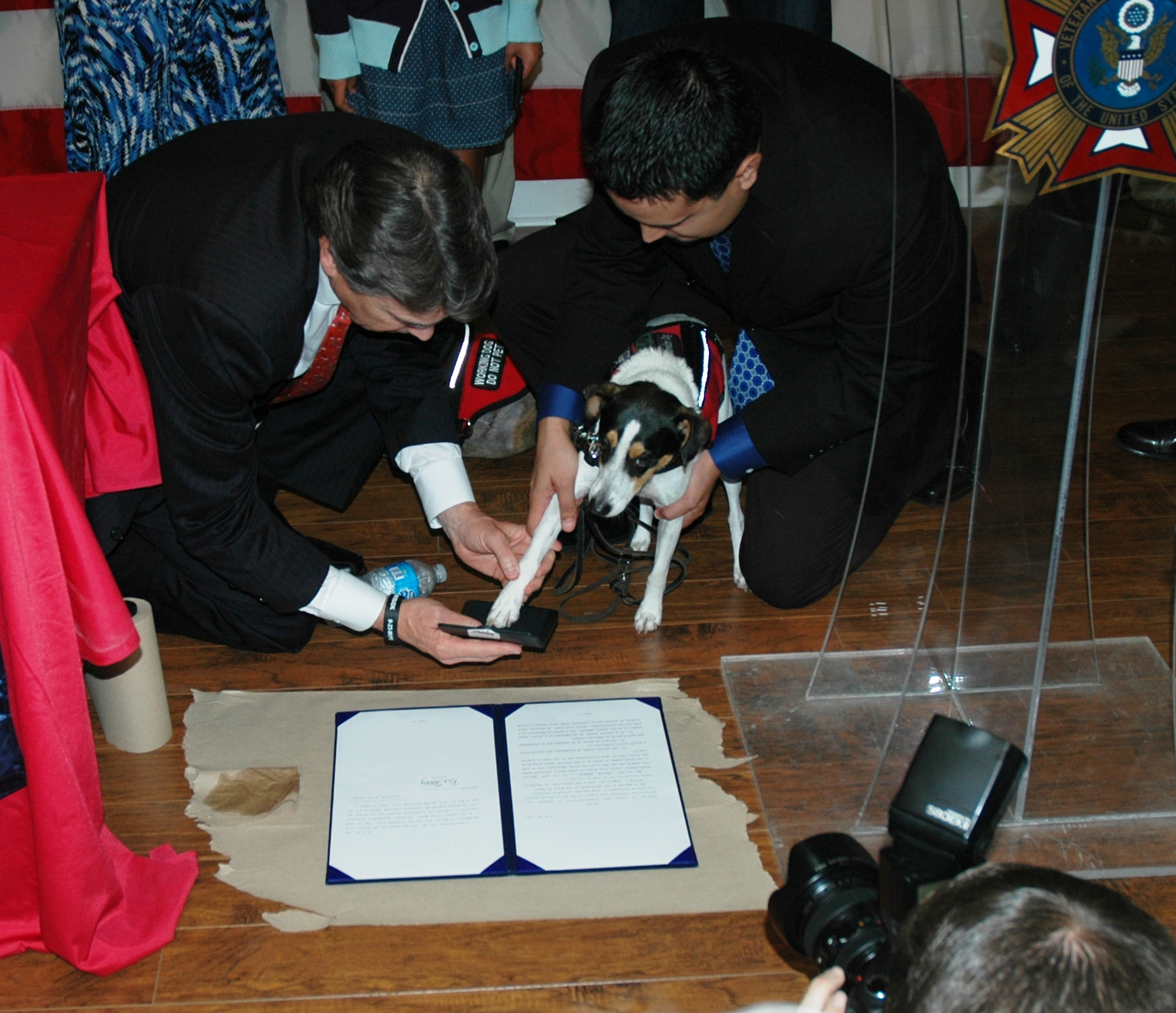 former Texas governor Rick Perry helping Bootz the dog put paw print on new law