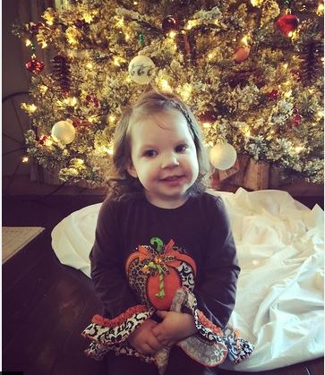photo of little Haylee in front of Christmas tree
