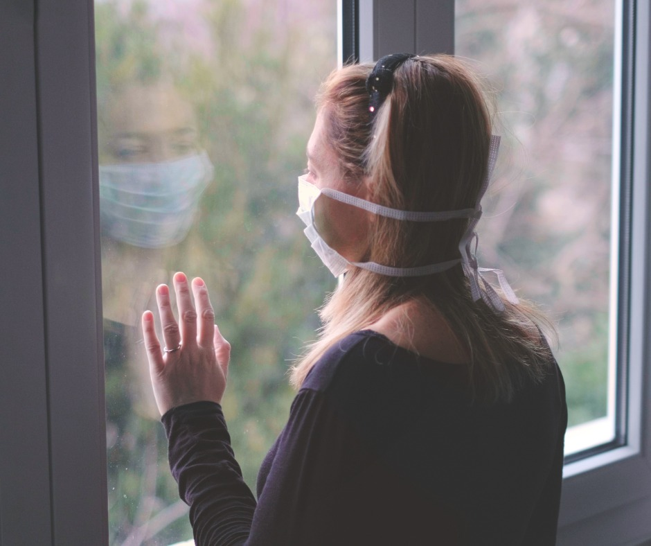 Woman alone with hospital mask staring out window