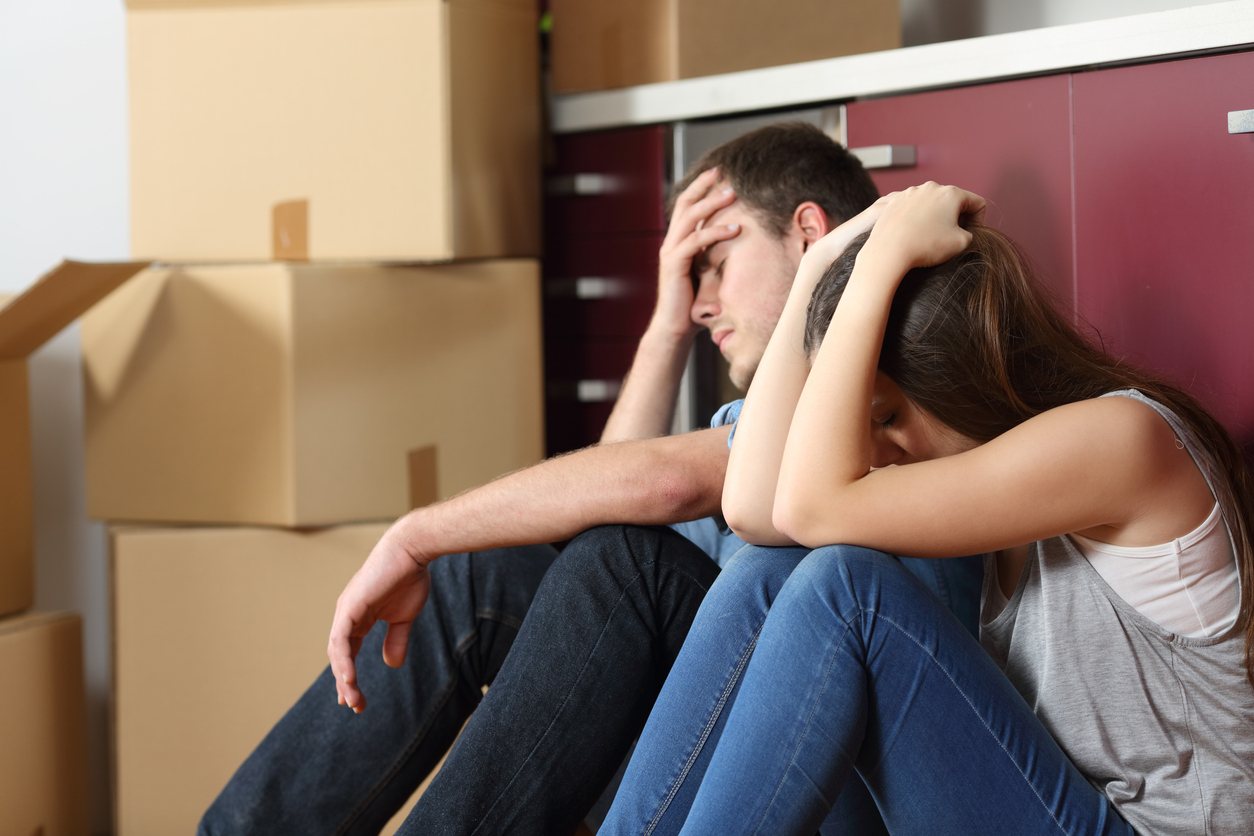 couple sitting on floor with hands on head with boxes in background